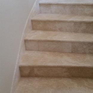 Idee per una scala curva classica con pedata in pietra calcarea e alzata in travertino