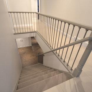 Ispirazione per una scala a rampa dritta minimalista con pedata in moquette e alzata in moquette