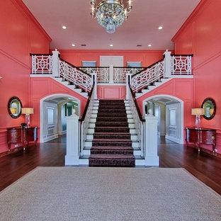 Exemple d'un très grand escalier chic en L avec des marches en moquette, des contremarches en moquette et un garde-corps en bois.