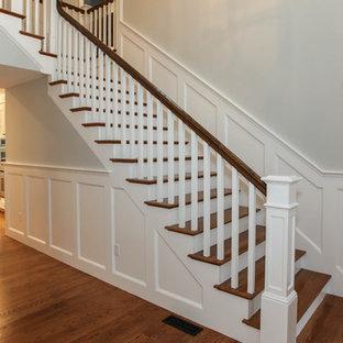 Imagen de escalera en L, de estilo americano, extra grande, con escalones de madera y contrahuellas de madera pintada