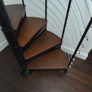 Ejemplo de escalera de caracol, industrial, pequeña, con escalones de madera y barandilla de metal