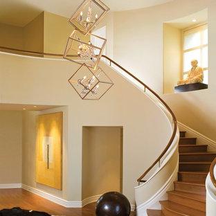 Idée de décoration pour un grand escalier courbe design avec des marches en bois, des contremarches en bois et un garde-corps en bois.