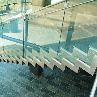 Imagen de escalera curva, minimalista, grande, con escalones de metal y contrahuellas con baldosas y/o azulejos