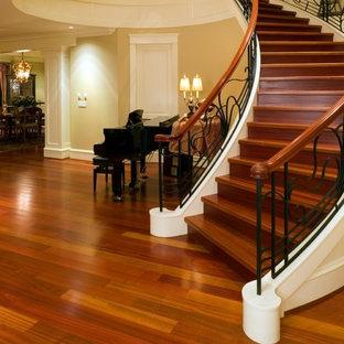 Ispirazione per una scala curva tradizionale di medie dimensioni con pedata in legno, alzata in legno e parapetto in legno