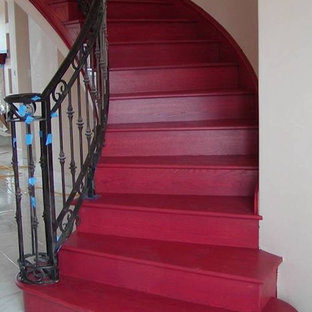 Staircase - large southwestern painted curved staircase idea in Austin with painted risers