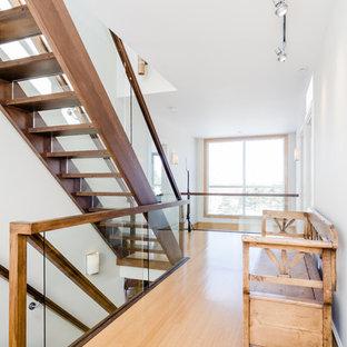 Modelo de escalera recta, actual, grande, con escalones de madera, contrahuellas de vidrio y barandilla de vidrio