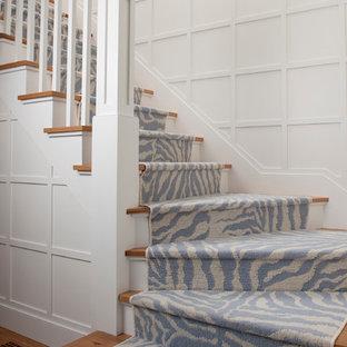 Modelo de escalera curva, tradicional renovada, de tamaño medio, con escalones de madera, contrahuellas de madera pintada y barandilla de madera