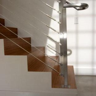 Ispirazione per una piccola scala a rampa dritta moderna con pedata in metallo e alzata in legno