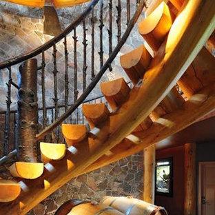 Ejemplo de escalera curva, rural, grande, sin contrahuella, con escalones de madera y barandilla de metal