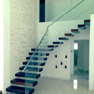Staircase - huge transitional wooden l-shaped staircase idea in Miami with glass risers
