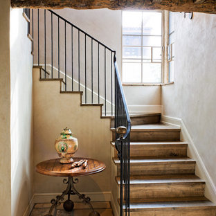 Staircase - rustic wooden u-shaped metal railing staircase idea in Phoenix with wooden risers
