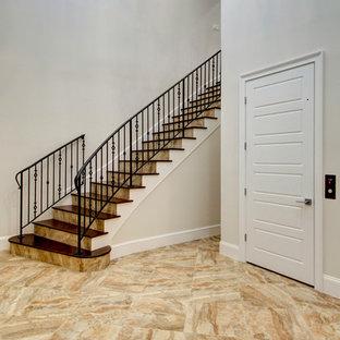 ジャクソンビルの大きい木のトラディショナルスタイルのおしゃれなサーキュラー階段 (タイルの蹴込み板、金属の手すり) の写真