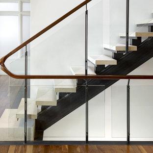 Modelo de escalera recta, urbana, sin contrahuella, con barandilla de vidrio y escalones de piedra caliza