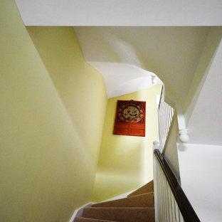 Foto di una grande scala curva vittoriana con pedata in moquette e alzata in moquette