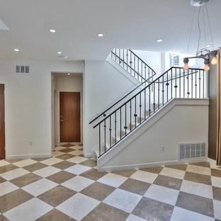 Diseño de escalera en L, tradicional, con escalones de travertino, contrahuellas de travertino y barandilla de metal