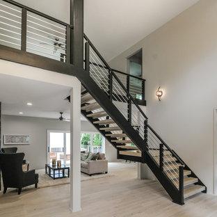 Diseño de escalera suspendida, moderna, grande, sin contrahuella, con escalones de madera y barandilla de metal