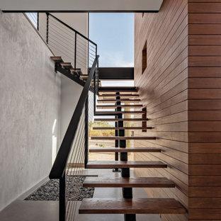 Foto di una scala sospesa minimal con pedata in legno, nessuna alzata, parapetto in cavi e pareti in legno