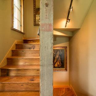 他の地域の中くらいの木のラスティックスタイルのおしゃれな折り返し階段 (木の蹴込み板、金属の手すり) の写真