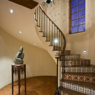 Staircase - mediterranean wooden curved staircase idea in Phoenix with tile risers