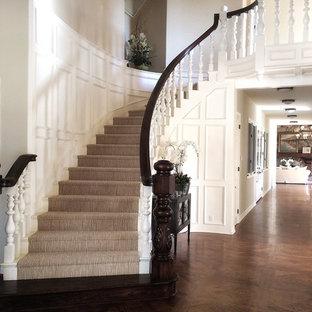Imagen de escalera curva, de estilo de casa de campo, grande, con escalones enmoquetados, contrahuellas enmoquetadas y barandilla de madera
