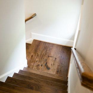 Foto de escalera en L, de estilo americano, de tamaño medio, con escalones de madera, contrahuellas de madera y barandilla de madera