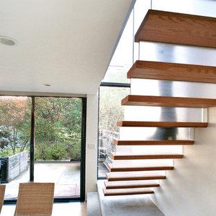 ニューヨークの中サイズの木のコンテンポラリースタイルのおしゃれな直階段 (ガラスの蹴込み板) の写真