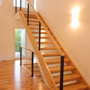 Immagine di una piccola scala a rampa dritta minimalista con pedata in legno, alzata in legno e parapetto in cavi