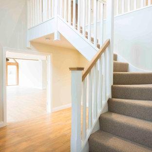 Diseño de escalera en L, campestre, grande, con escalones enmoquetados, contrahuellas enmoquetadas y barandilla de madera