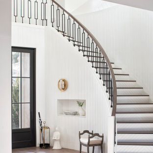 This is an example of a transitional wood curved staircase in Miami with painted wood risers and mixed railing.