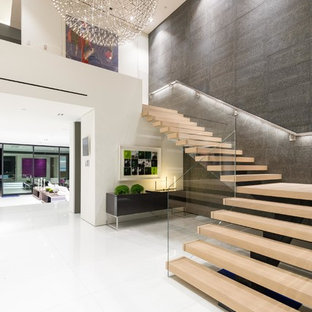 Inspiration for an expansive modern wood l-shaped glass railing staircase in Los Angeles with open risers.