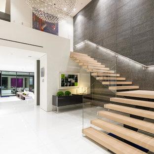 """Immagine di un'ampia scala a """"L"""" minimalista con pedata in legno, nessuna alzata e parapetto in vetro"""