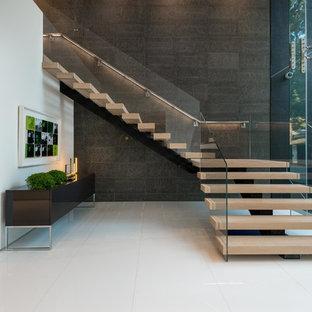 Réalisation d'un très grand escalier sans contremarche minimaliste en L avec des marches en bois et un garde-corps en verre.