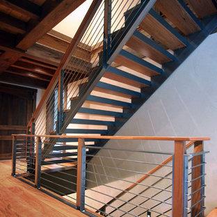Ejemplo de escalera suspendida, de estilo americano, con escalones de madera y contrahuellas de metal