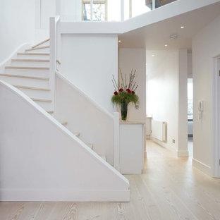 Foto de escalera curva, escandinava, de tamaño medio, con escalones de madera y contrahuellas de madera pintada