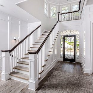 Example of a classic wooden u-shaped wood railing staircase design in Los Angeles with wooden risers