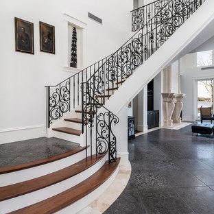 Diseño de escalera curva, mediterránea, grande, con escalones de madera, barandilla de metal y contrahuellas de travertino