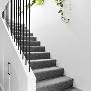 Inspiration för en liten nordisk l-trappa, med heltäckningsmatta, sättsteg med heltäckningsmatta och räcke i metall