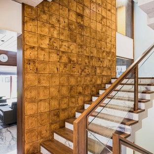 Foto de escalera en U, asiática, con escalones de madera, contrahuellas de mármol y barandilla de vidrio