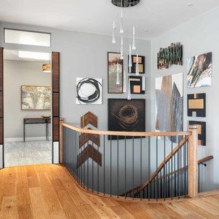 Foto di una scala a chiocciola design di medie dimensioni con pedata in metallo, alzata in legno e parapetto in legno