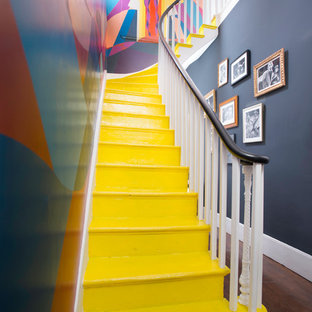 This is an example of an eclectic painted wood l-shaped staircase in London with painted wood risers.