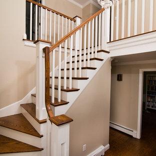 Ispirazione per una scala curva moderna di medie dimensioni con pedata in legno e alzata in legno verniciato