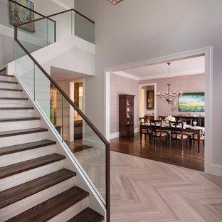 Imagen de escalera en L, clásica renovada, con escalones de madera, barandilla de vidrio y contrahuellas con baldosas y/o azulejos