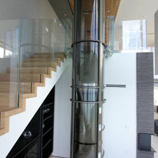 """Idee per una grande scala a """"L"""" minimalista con pedata in legno, alzata in legno, parapetto in vetro e carta da parati"""