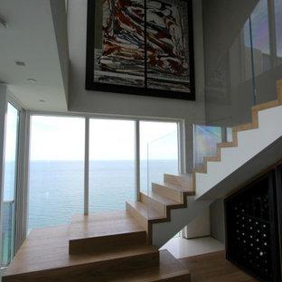 Modelo de escalera en L y papel pintado, minimalista, grande, con escalones de madera, contrahuellas de madera, barandilla de vidrio y papel pintado