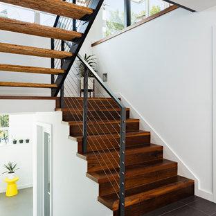シアトルの木のコンテンポラリースタイルのおしゃれな折り返し階段 (木の蹴込み板、ワイヤーの手すり) の写真