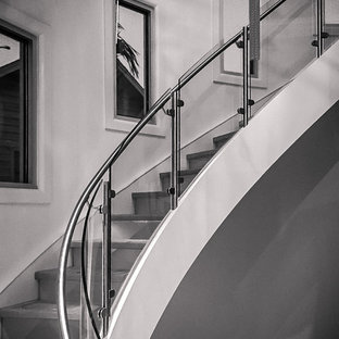 Example of a huge minimalist wooden curved staircase design in Atlanta with glass risers