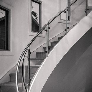 Idee per un'ampia scala curva minimalista con pedata in legno e alzata in vetro