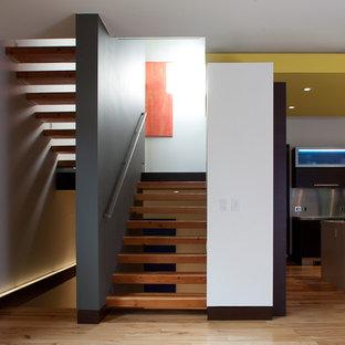 Ispirazione per una scala sospesa design con pedata in legno e nessuna alzata