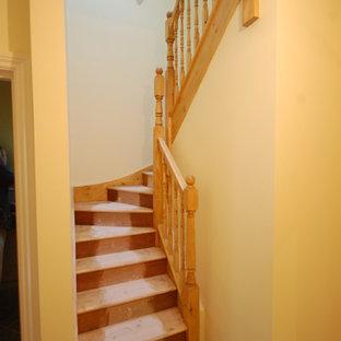 "Foto di una scala a ""U"" classica di medie dimensioni con pedata in legno e alzata in legno"