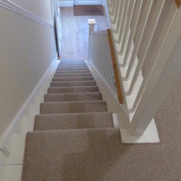 plain stair carpet runner leading to engineered oak hall